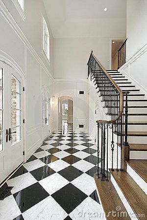 love the idea of a foyer of black and white tile with dark handrail.