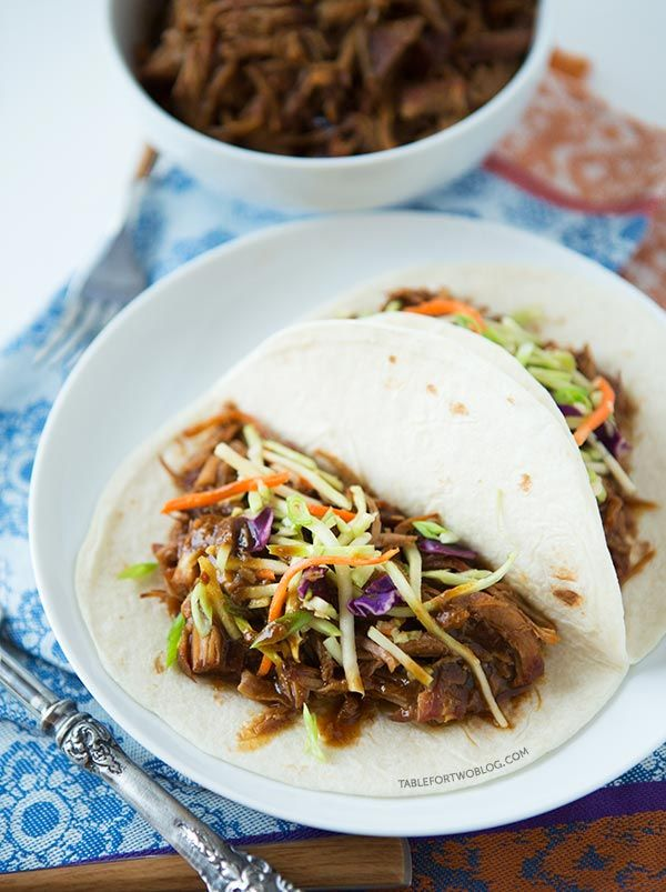 ... pork is wrapped inside a warm tortilla and topped with a tangy slaw