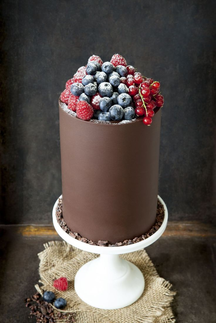 Chocolate cake with berries - Beautiful. Covering a cake in solid chocolate is actually easy.  Spread tempered chocolate on acetate or parchment, then wrap it around a crumb-coated or fully, but smoothly frosted cake and tape (or seal with chocolate) the ends.  Set in fridge then gently peel off.