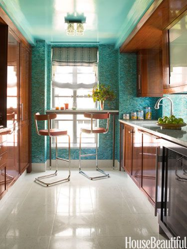 In this kitchen, iridescent mosaic tiles and a ceiling lacquered in Benjamin Moore's Oceanic Teal pick up a color from the wallpaper in the hallway.