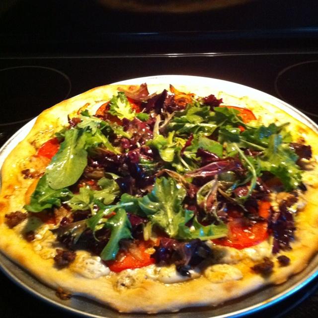 Tomato and mozzarella pizza topped with arugula salad