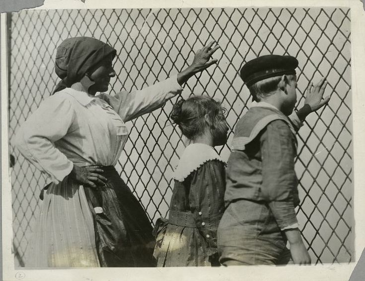A woman, a boy and a girl at a chain link fence, Ellis Island, New York. (Lewis W. Hine)