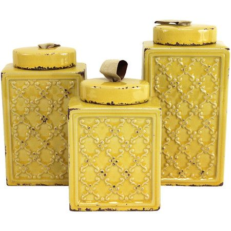 set of three weathered metal canisters in yellow with a scrolling
