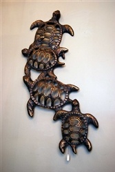 Family of three attatched metal turtles wall hanging.