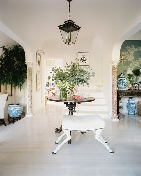 A quirky animal-hooved bench stands guard in a bright  white entry hall.  Green foliage dresses every corner of the adjoining rooms.