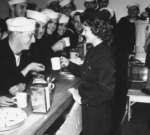 Myrna Loy serving coffee to service men