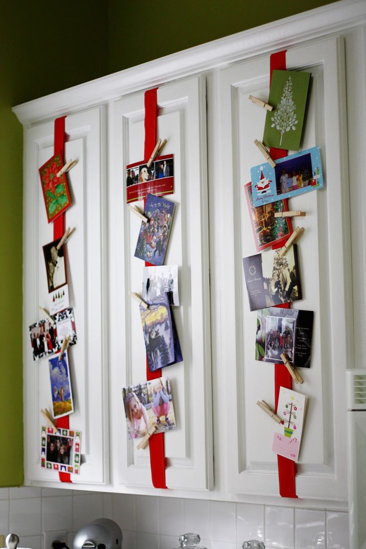 "Good idea for Christmas cards! Attach ribbon to kitchen cabinets. Use clothespins to hang cards. This is from the blog ""Greener Grass."""