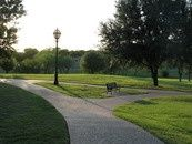 This serene 13 acre park, of which 2.50 acres is leased, is located adjacent to the A. W. Perry Museum and was dedicated to the city by Mrs. Pearl Perry Gravley. Visitors can enjoy a free tour of the museum and stroll the passive park setting. Facilities include walking paths, park benches, water fountain, and parking lot. Bikes and skateboards are prohibited.