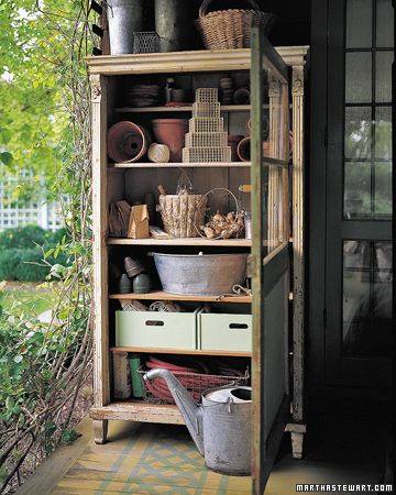 a wooden cabinet serves as a potting shed.