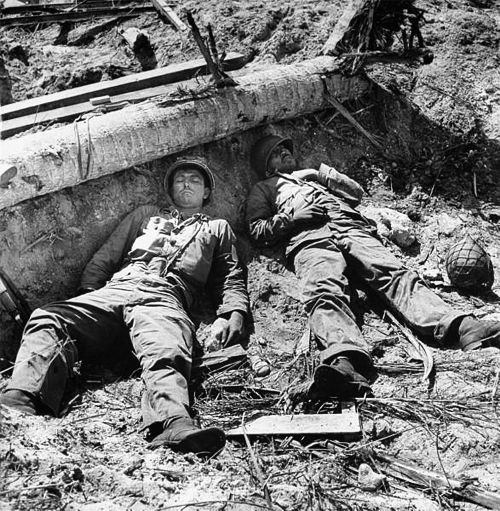 Two US Marines, exhausted from earlier fire fights, sleep on the front lines somewhere during the Marshall Island campaign.