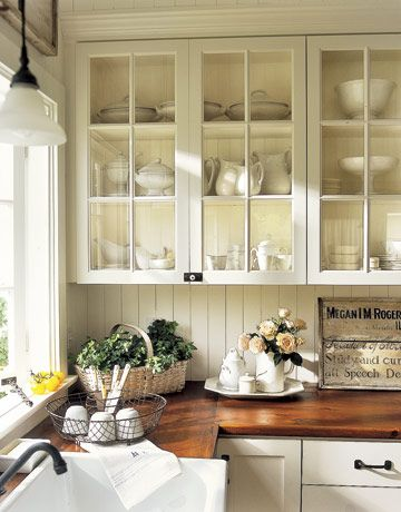 I really love this kitchen - vintage looking white cabinets, some with glass, beading board backsplash and an awesome wood countertop from salvaged flooring.