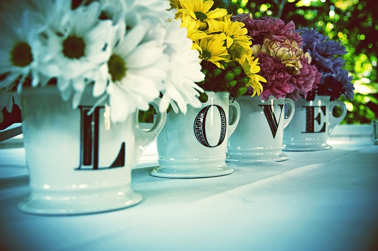 """My sister turned me on to these monogram mugs from Anthropologie (one of our fav stores) & I saw a pic of them spelling """"L.O.V.E"""" with flowers in them from a magazine or online & knew where to get them & HAD to have the mini arrangements on my cake (and seating chart) table on my special day! Our guests loved them! :)"""
