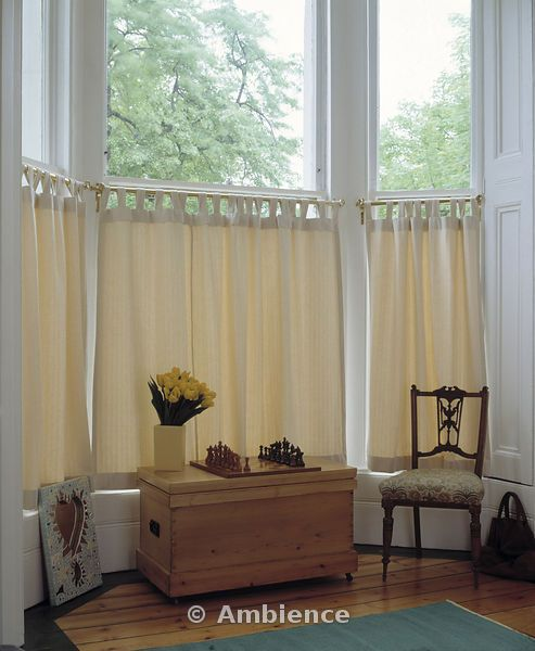 Bay window cafe tier curtains in solid cream color and curved rods