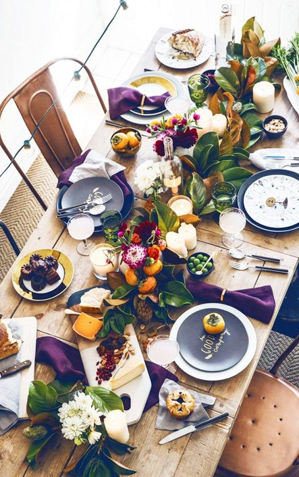 Green and purple Thanksgiving table with persimmons and green leaf floral table settings.