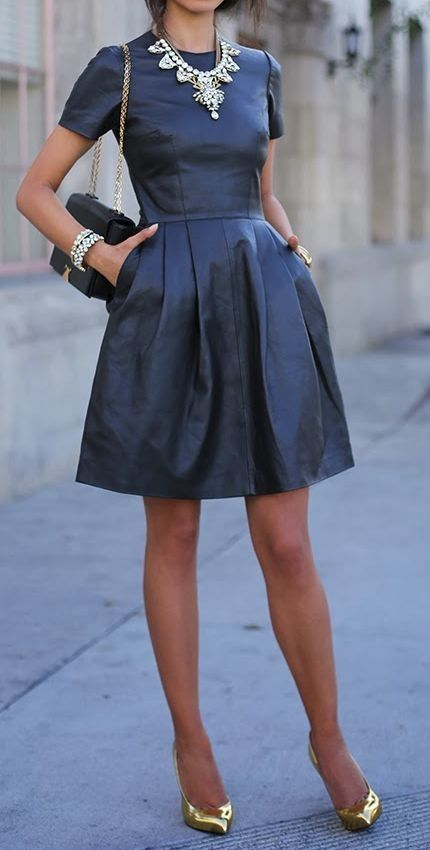 Black leather dress with awesome necklace and gold nude pumps.