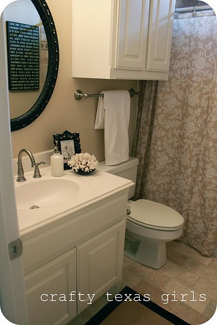 Small bath like ours. White Vanity, Oval Dark mirror, light walls, beige shower curtain with window and towel bar and cabinet above toilet.