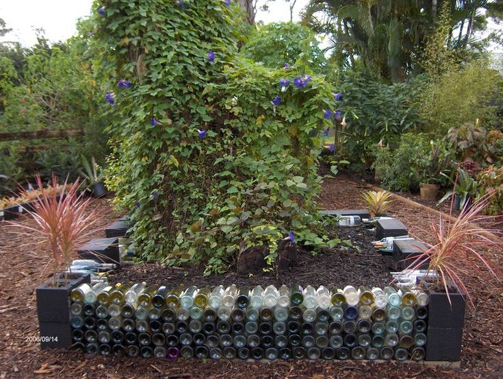 The county won't pick up our recycled glass so it stacks up in the garage... BINGO! Wine bottle raised beds. XOXO