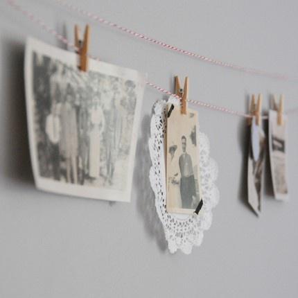 Um pequeno varal de fotos polaroid abaixo de uma das prateleiras na parede.