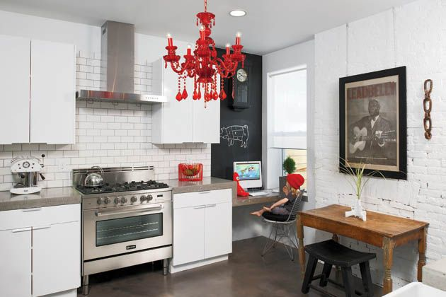 The White Kitchen Is Warm And Inviting With Bursts Of Red Accent