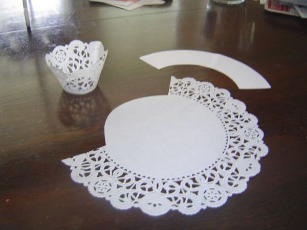 Cut a section of paper doily, tape, and presto!  Easy lace cupcake wrap!
