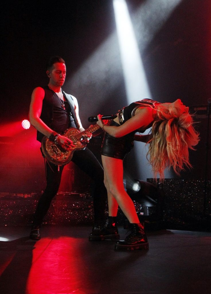 "Now that's what we call ""Hanging On."" The spotlight shines on a back-bending Ellie Goulding as she feeds off guitarist Chris Ketley during a performance on Oct. 16 in London"