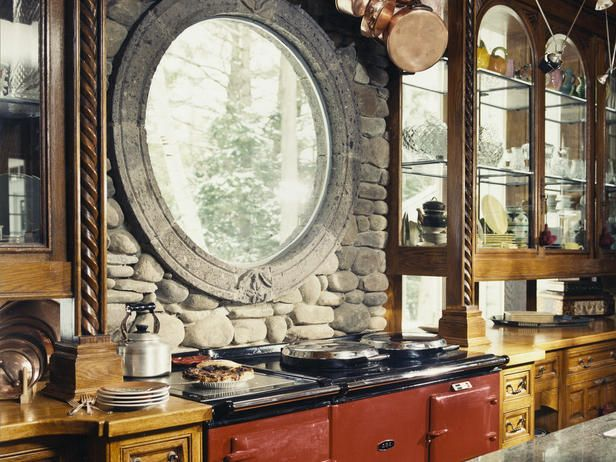 For an Old World look, this red AGA cooker is complemented with circular window surrounded by rustic stone. #hgtv