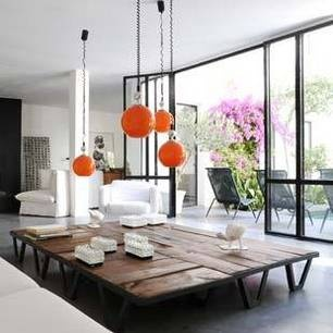 a huge coffee table is a fantastic idea. can't tell if this is all one piece, or several that could be moved apart. loving the orange glass pendants too