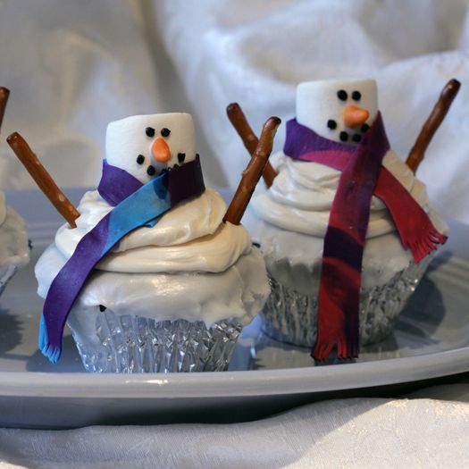 Snowman Cupcakes -- See how easy it is to use homemade or prepared cupcakes, some Cake Make icing and decorating products, marshmallows and #SnydersOfHanover #pretzels to make adorable #snowman #cupcakes