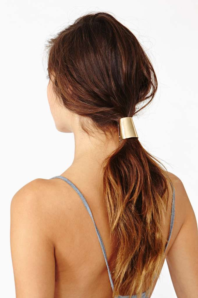 Insanely rad gold ponytail clip featuring a cylindrical design and spring closure. Black rubber band attached inside. Slick back your hair and add this for a clean minimal look!