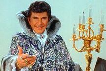 """Liberace! / Born less than 10 miles from where Milwaukee Rep now stands, Liberace lived a life of flamboyance, flash, and lavish costumes. In this funny and touching tribute, the virtuoso musician gets one last chance to glitter and shine as he tickles the ivories through his favorite songs, including """"I'll Be Seeing You,"""" """"Chopsticks,"""" and """"The Boogie Woogie."""" Milwaukee favorite, Jack Forbes Wilson, will reprise his iconic performance as the man who defined four decades of music and pop culture. / by Milwaukee Rep"""