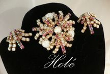 "Hobe Jewelry / Legend has it that Florence Ziegfield purchased a large order of costumes for the famed Zigfield Follies from Hobe & requested that he create inexpensive but real looking jewelry to compliment the showgirls' costumes. Thus, the term ""costume jewelry"" was 1st used. Hobe jewelry shows excellent & elegant designs with high quality stones & superior silver or gold plated metalwork. Especially on its reproductions of antique jewelry which employed handset semiprecious stones & multicolored enamelwork / by Dawn McNeal"
