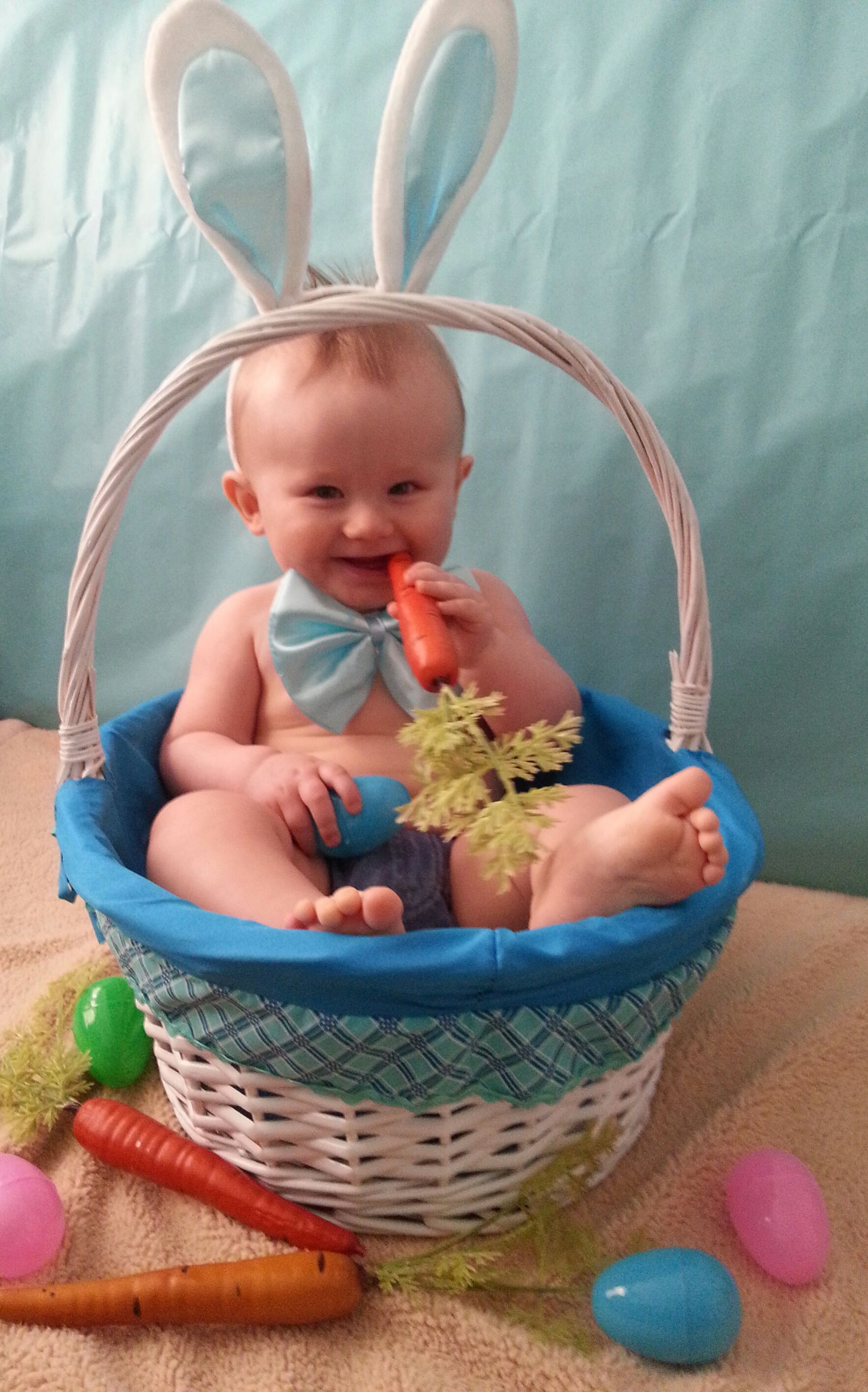 Easter conceptual image on blue wooden background with copyspace chocolate easter rabbit, candy, sweets, baby chicken and easter eggs in basket. Kids celebrate easter. Family happy little girl boy and baby in bunny ears on a couch.