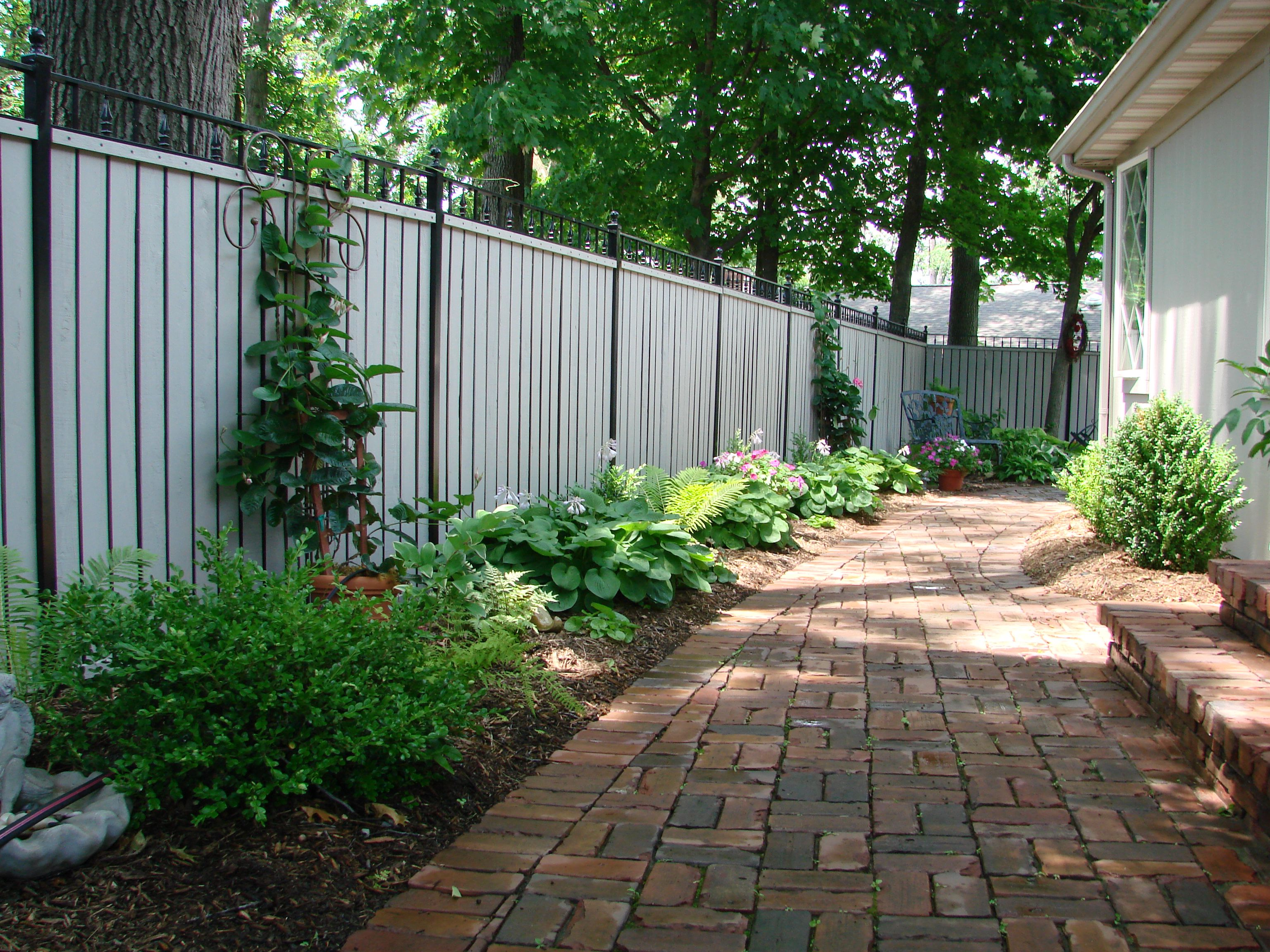 Landscaping along fence and pavers outdoor spaces for Garden along fence