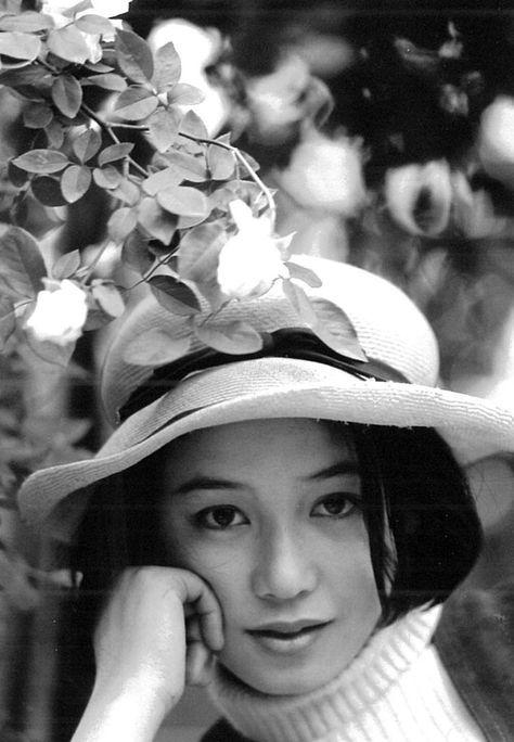 花の下で帽子をかぶって頬杖をついているひし美ゆり子の画像