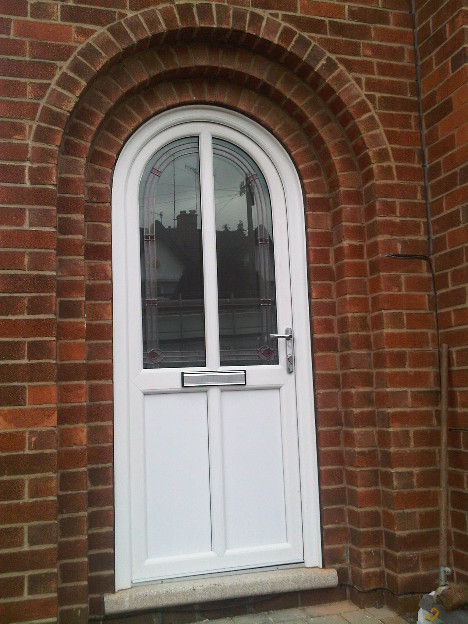 Arched front door in white upvc making an entrance for Upvc front doors