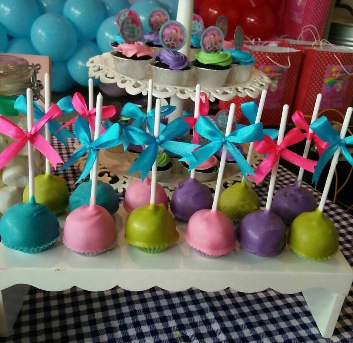 Examples of Pink, Purple, Blue, and Green JoJo Siwa Cake Pops with Bows Attached