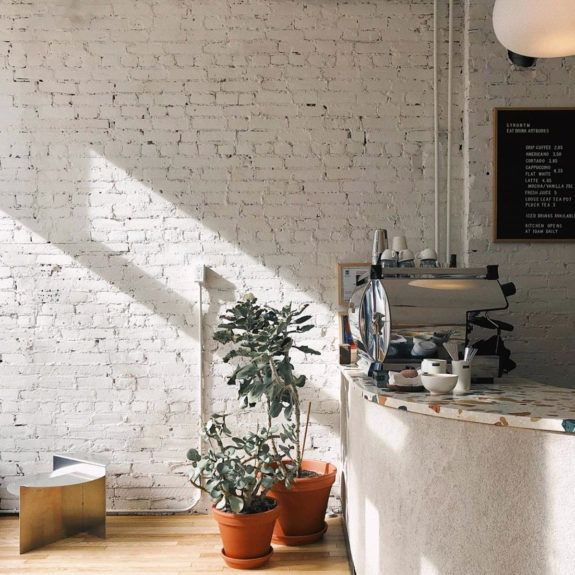 white painted brick walls and terrazzo countertop inside hamilton, canada coffee shop, synonym. #coffeeshop #coffee #store #design #decor #whitebrick #paintedbrick #brick #exposedbrick #indoorplants #pottedplants #plants #terrazzo #counter #bar