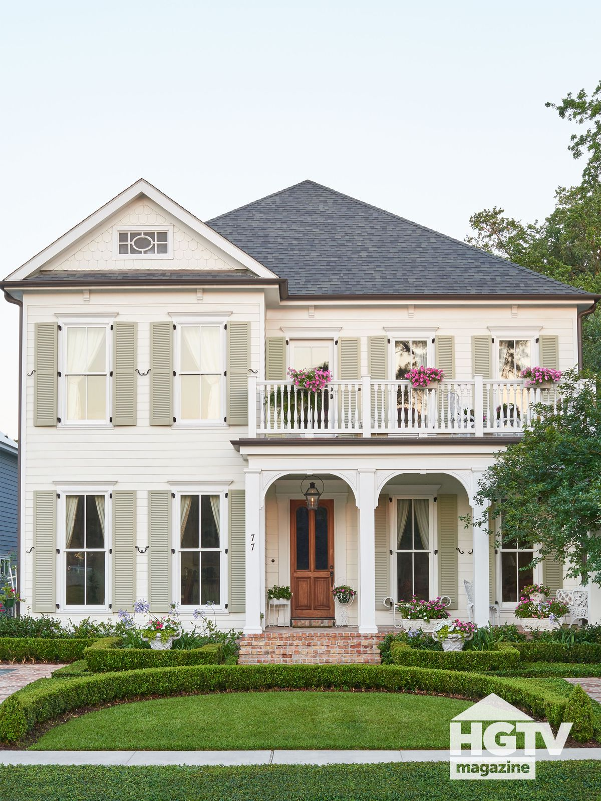 A neutral colored home with sage green shutters from HGTV Magazine
