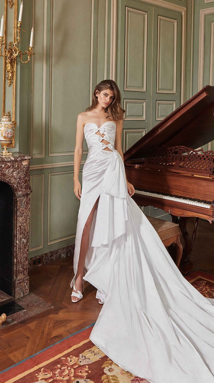 Sexy and elegant our #Margaret is a dramatically draped ball gown with cutouts and silk bows, this asymmetrical stunner features a high slit and a side bow in a soft silk duchess satin.