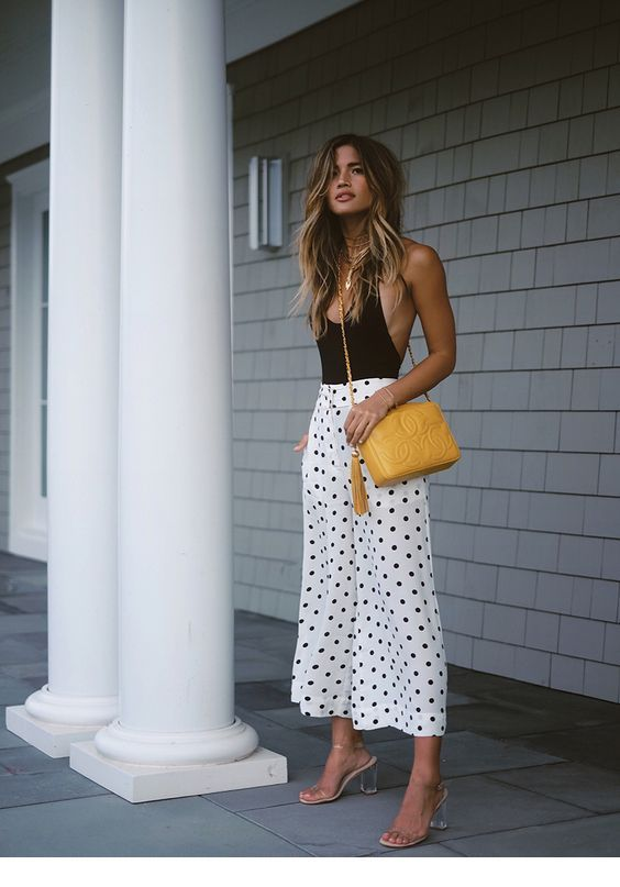 Black top, polka dots skirt and a yellow bag