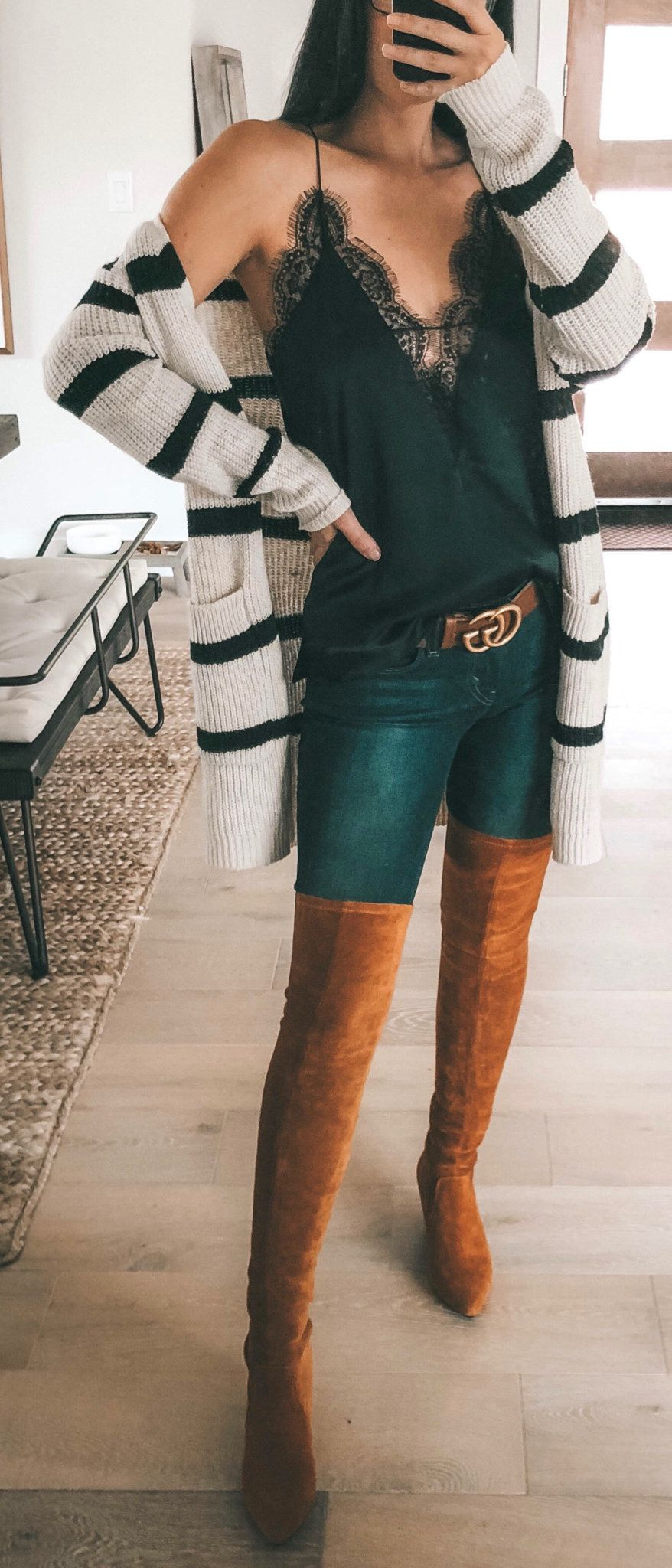 black and white striped blazer, green top, and pair of boots