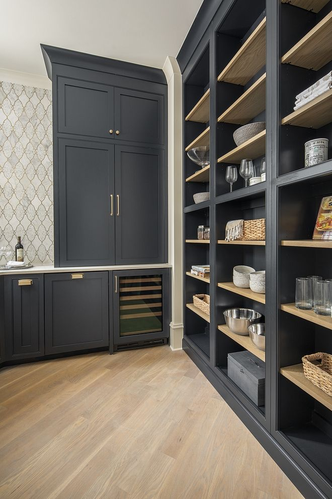 Benjamin Moore Soot Pantry Pantry is adjacent to the kitchen through a cased opening, and functions as a perfect spot for additional storage, wine storage, a coffee station, and much more. The builder added a large wall of open bookcase style shelving to cover one wall and it can be used to store fine china, bar ware, cookbooks, etc Cabinet color is Benjamin Moore Soot 2129-20 #BenjaminMooreSoot #Pantry