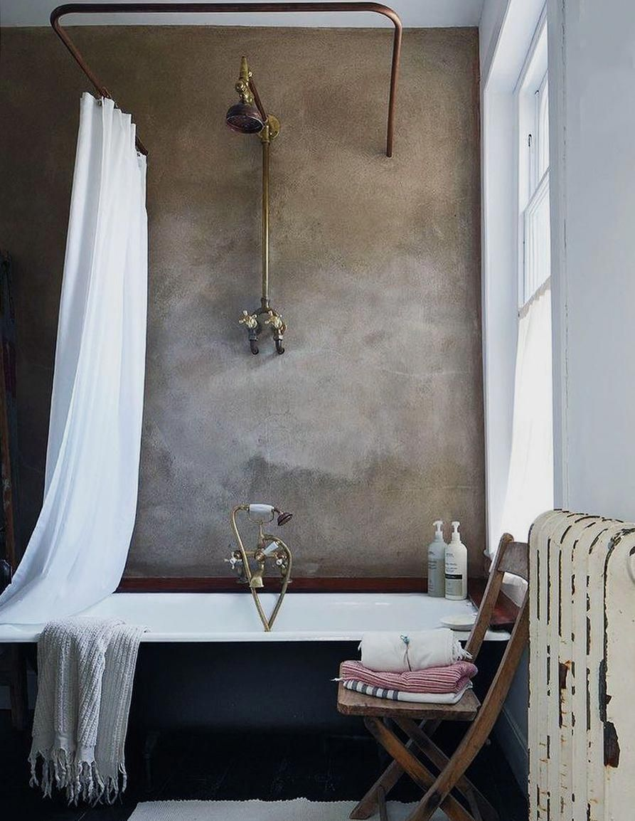 vintage inspired bathroom with concrete walls and industrial pipe shower curtain rod with clawfoot bathtub. / sfgirlbybay #vintageBathroom