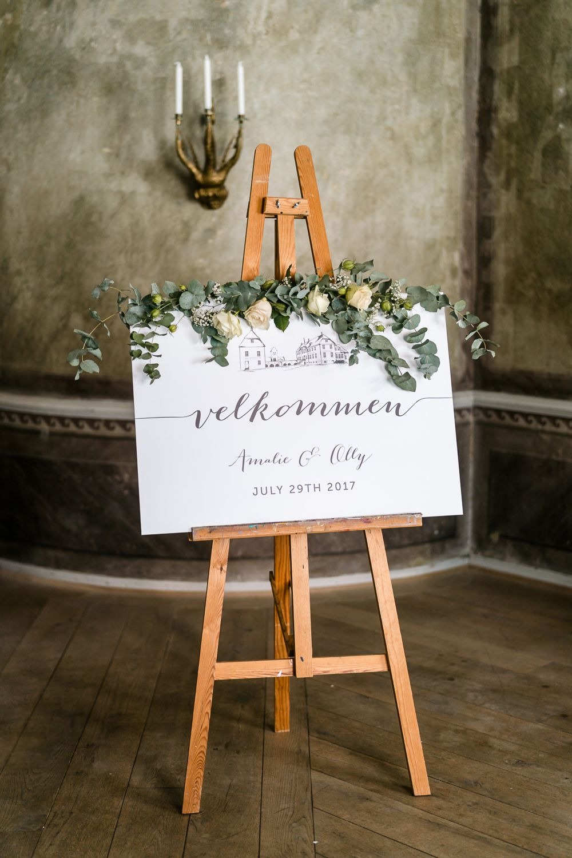 Welcome Sign on Easel | Traditional Green/Blue Danish Wedding at Scandinavian Country House, Jomfruens Egede in Faxe, Denmark | John Barwood Photography