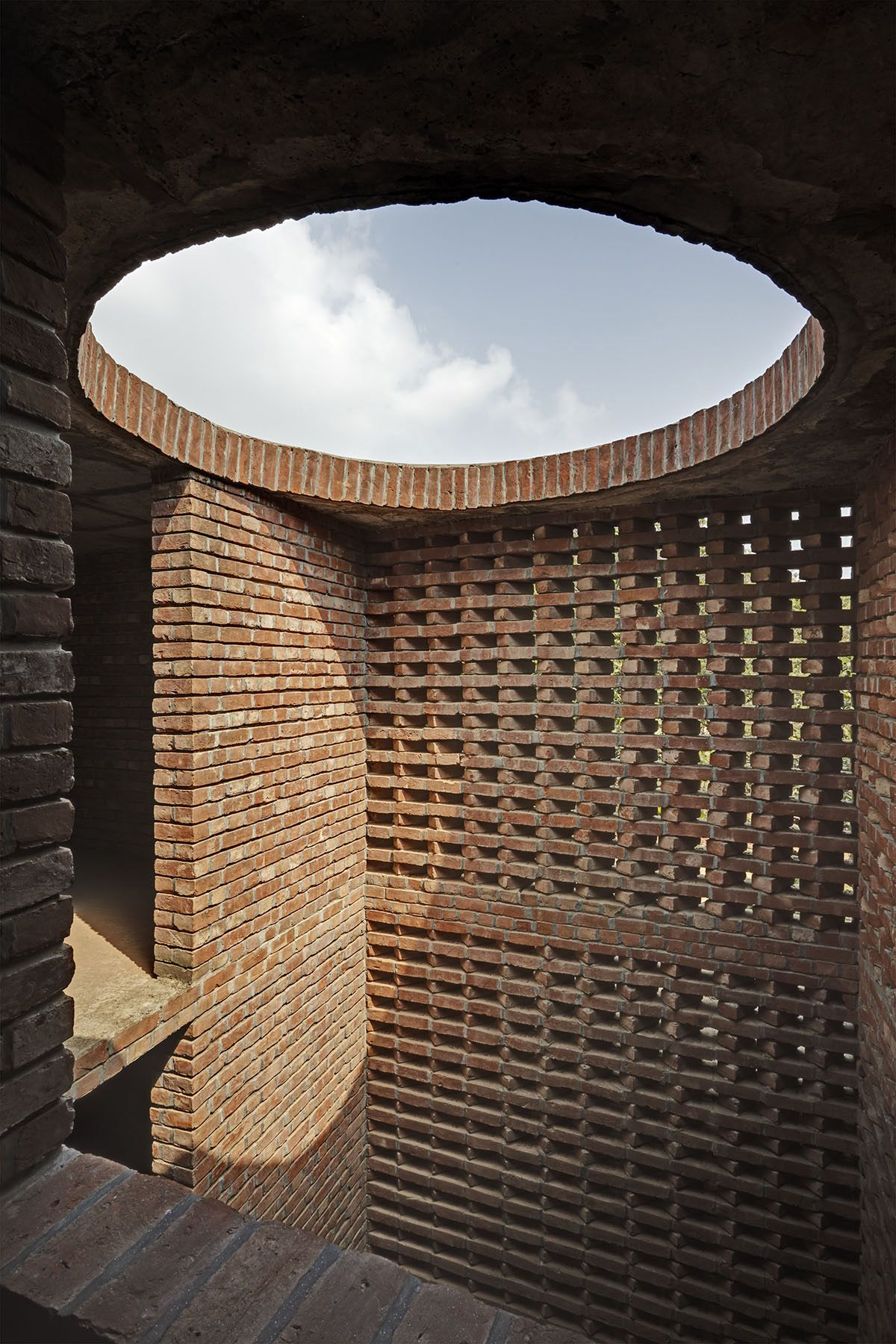 The prayer hall separates itself from the rest of the structure by open-to-sky light wells between the cylinder and the inner square. Light pours down on the unplastered brick walls, giving it a primordial character | Archnet