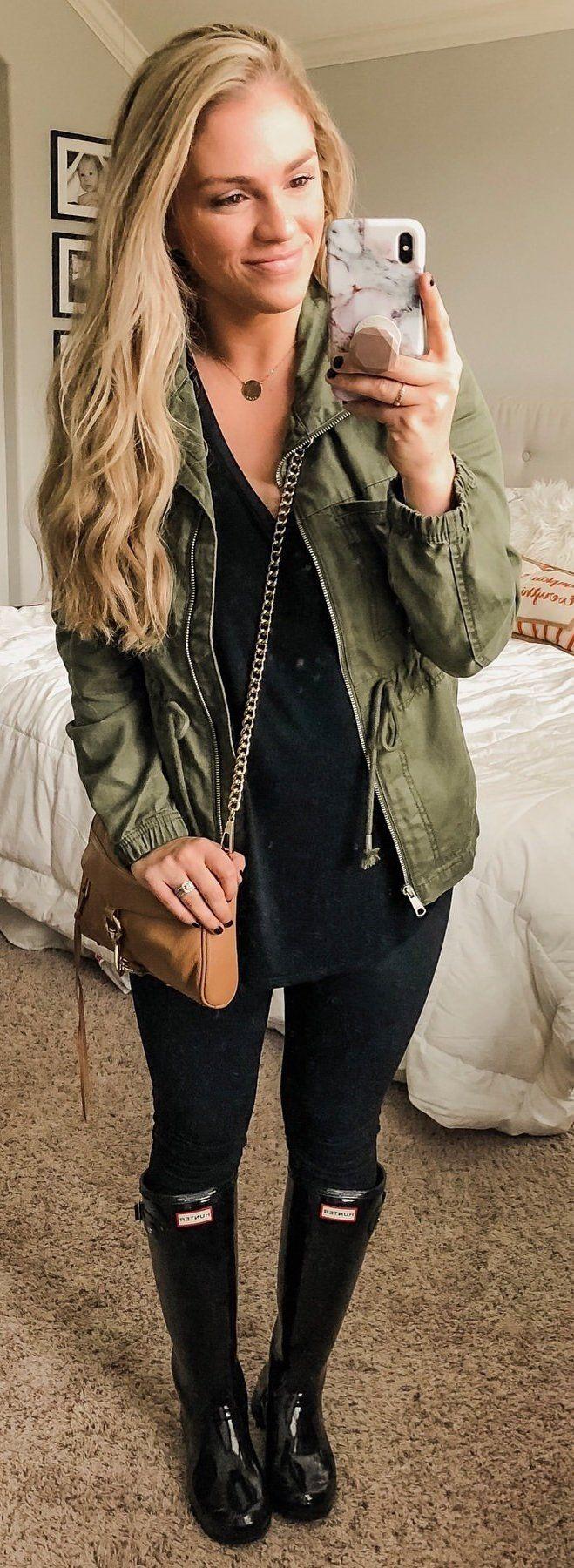 black plunging neckline shirt and green zip-up jacket