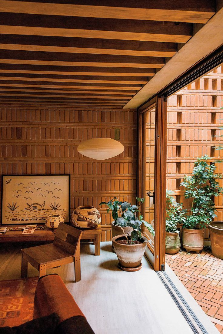 In the living room, a Noguchi lamp hangs over a group of native plants. The drawing is by the Cuban artist José Bedia, and the 1930s chair is from northern Mexico.