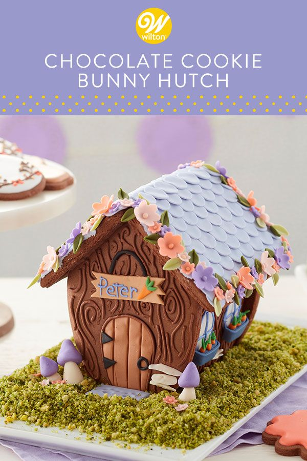 Sweeten your spring celebration with this Chocolate Cookie Bunny Hutch. Made using our Bunny Hutch Cookie Kit and decorated with fondant flowers and embellishments, this cute little hut is a great centerpiece for your Easter table or baby shower. Personalize the hutch with a name of your choosing. #wiltoncakes #cookiehouse #cookiekit #cookiedecorating #homemade #easter #kidsacticity #easterbunny #easteractivity #familytime #cookieideas #dessert #springtime #spring #springdesserts #fondant