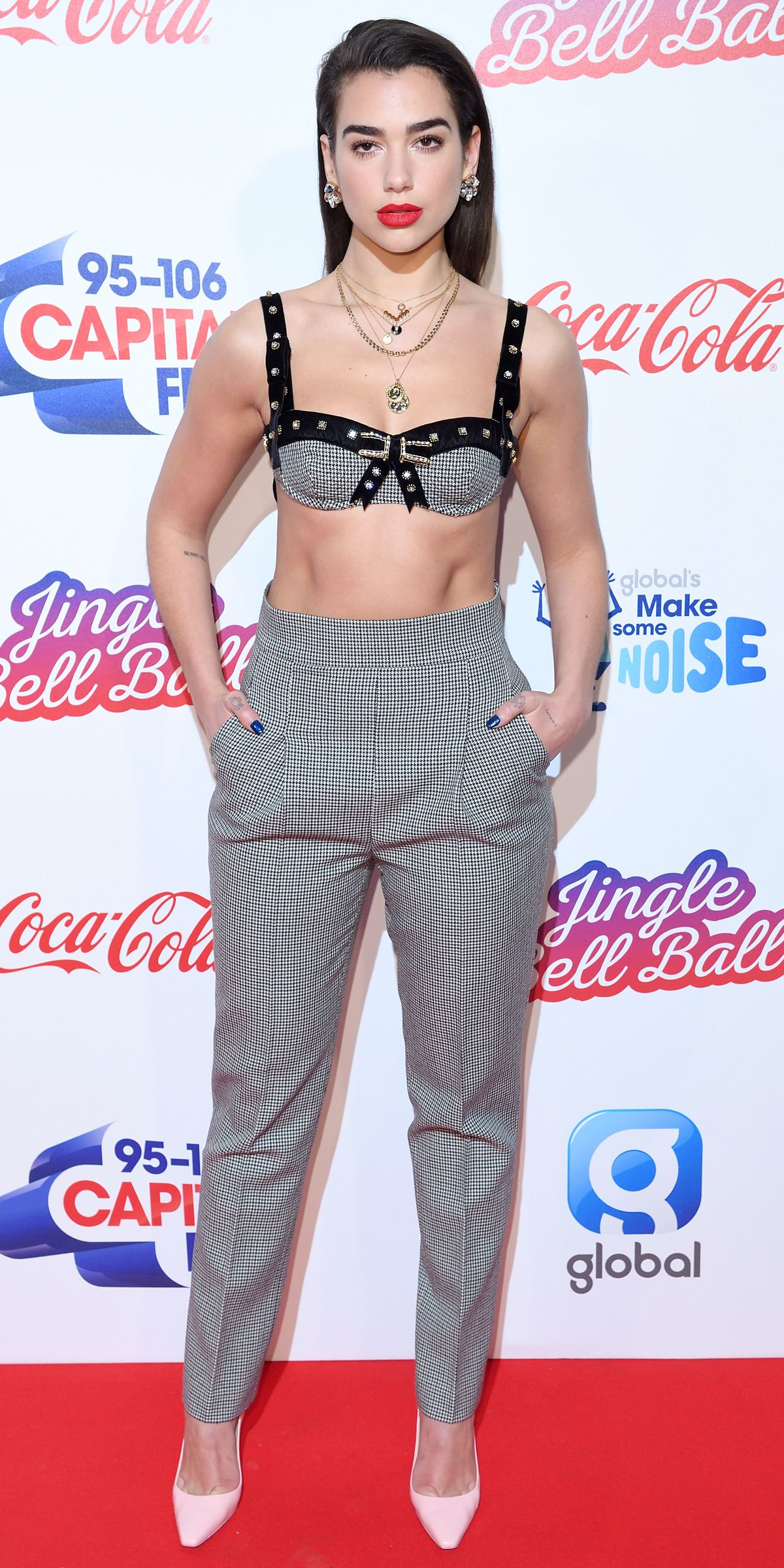 At the Jingle Bell Ball in London, British singer Dua Lipa put a feminine twist on menswear dressing with a velvet-trimmed bralette by Philosophy Di Lorenzo Serafini. We're freaking out because those classic pants are 50 percent off at Farfetch right now.