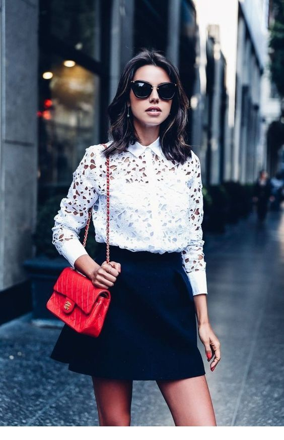 White lace shirt, mini black skirt and a red bag